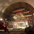 Podzemní katedrála: Banální obraz? Nikoliv, to si jen při prvním pohledu neuvědomujeme, kolik podlaží má pracovní plošina, jak nepřirozeně krátký je dilatační díl ostění, jak nepatrné jsou postavy dělníků. A najednou si začínáme všímat detailů. Za několik měsíců bude tato podzemní katedrála vyplněna příčkami a technologickým zařízením pro větrání rozsáhlého komplexu tunelů.
